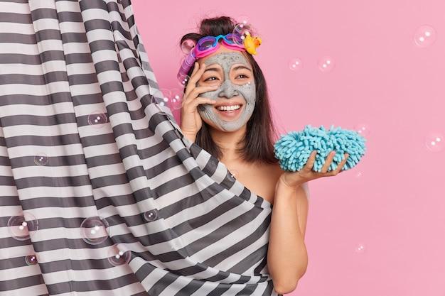 La donna asiatica abbastanza sognante fa la doccia mattutina a casa applica la maschera facciale di bellezza lava il corpo con una spugna e pulisce la pelle gode di procedure igieniche rinfrescanti
