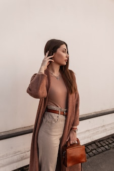 Giovane donna abbastanza elegante in cappotto alla moda in pantaloni con borsa marrone alla moda di cuoio che posa vicino all'edificio bianco sulla strada. la ragazza attraente dell'annata moderna cammina sulla città. look casual alla moda primaverile