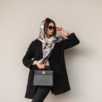 Piuttosto elegante giovane donna in scialle di seta di lusso sulla testa in cappotto nero elegante con borsa in pelle alla moda raddrizza occhiali da sole vintage vicino alla parete al chiuso. elegante modello di moda ragazza professionale moderna.