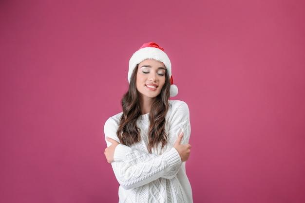Signora abbastanza emotiva con cappello di natale su sfondo colorato
