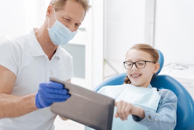 Adolescente abbastanza entusiasta che ascolta una conferenza sulla procedura che sta subendo e che fa molte domande al suo medico