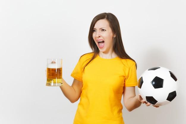Piuttosto europea giovane donna triste sconvolta, tifoso di calcio o giocatore in uniforme gialla tiene una pinta di birra, si preoccupa di perdere la squadra isolata su sfondo bianco. sport, giocare a calcio, concetto di stile di vita.