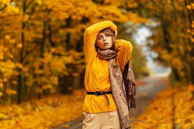 Bella modella caucasica di moda donna in maglione giallo lavorato a maglia vintage e sciarpa posa in un fantastico parco autunnale con foglie gialle
