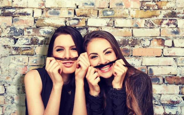 Belle donne alla moda che indossano abiti neri alla moda isolati su sfondo Foto Premium