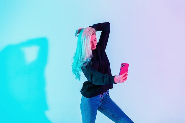 Donna bionda abbastanza alla moda in felpa con cappuccio nera casual con jeans blu fa una foto selfie su uno smartphone in studio su uno sfondo colorato rosa neon