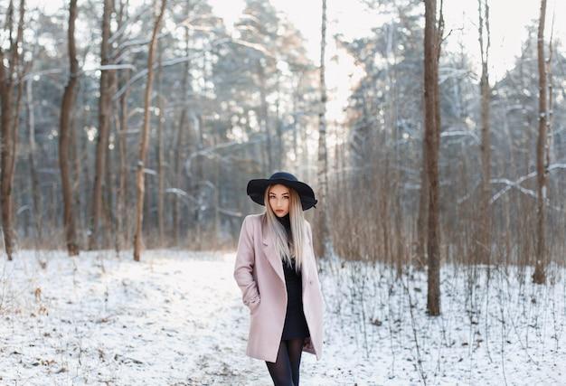 Donna abbastanza alla moda in cappello nero e cappotto rosa in boschi incredibili di inverno al tramonto
