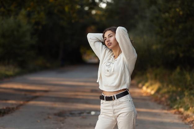Modello di donna abbastanza alla moda con capelli ricci in maglione lavorato a maglia vintage passeggiate nel parco all'aperto