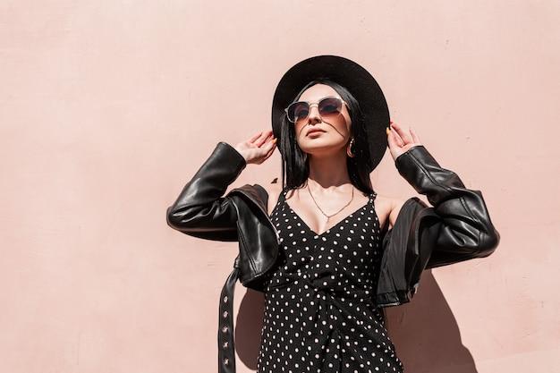 La giovane donna abbastanza alla moda in cappello in rivestimento in vestito in occhiali da sole gode del sole in città. modello di ragazza di moda ritratto soleggiato in vestiti neri eleganti estivi belli alla luce del sole vicino al muro rosa