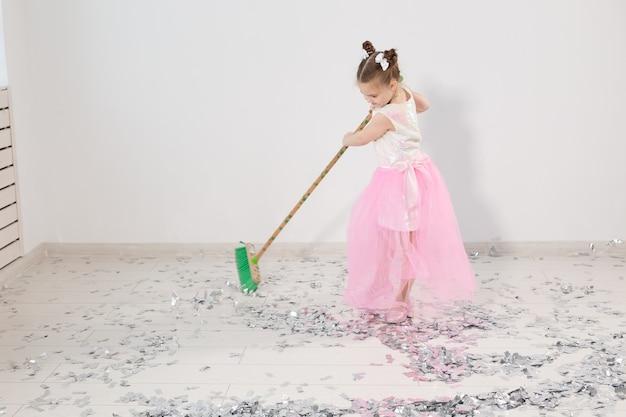 Appartamento di pulizia del bambino femminile grazioso dopo la festa di natale.