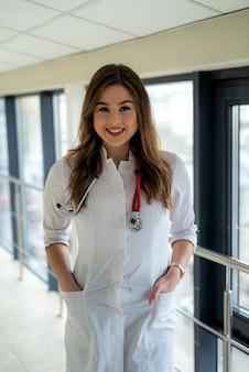 Bella dottoressa in camice bianco con stetoscopio al corridoio dell'ospedale