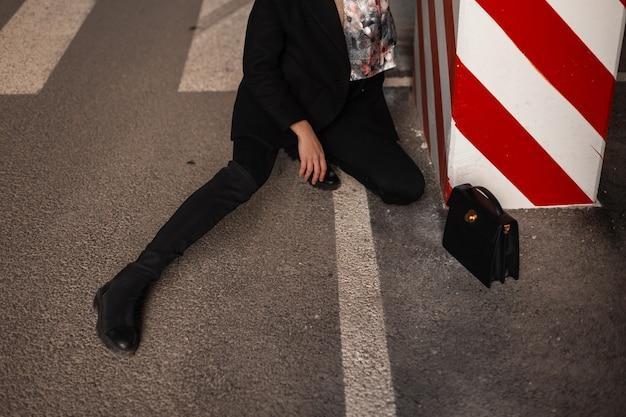 Gambe femminili graziose in jeans neri alla moda con borsa su asfalto