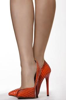 Piedini femminili graziosi in tacchi alti di pelle di serpente rossa