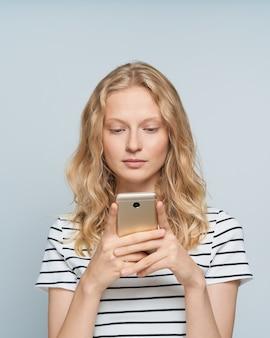 Media sociali alla ricerca abbastanza femminili sul telefono cellulare in piedi vicino al muro grigio bianco