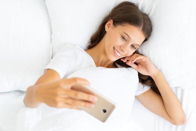 Selfie abbastanza femminile, bionda scatta foto sul telefono cellulare sdraiato a letto. bella donna e sorridente, amore per te stesso. vista dall'alto