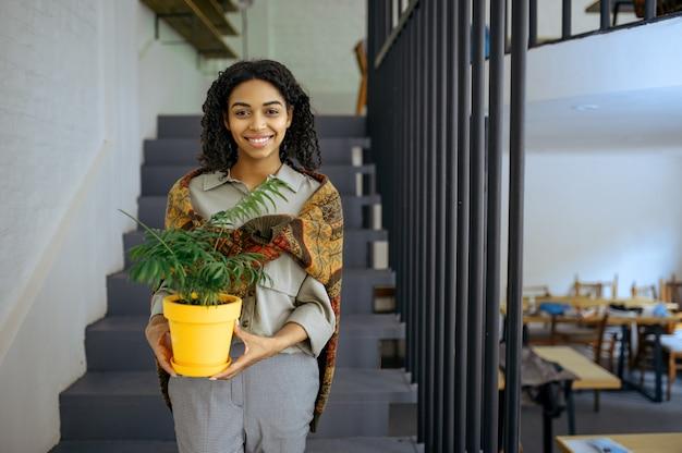 La studentessa graziosa tiene il fiore in una pentola sui gradini nella caffetteria della biblioteca. donna che impara una materia, un'istruzione e una conoscenza. ragazza che studia nel campus