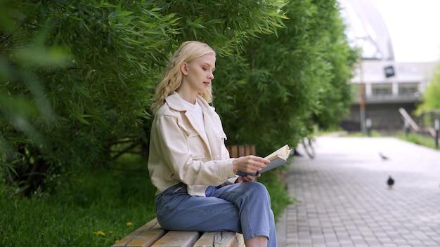 Bella studentessa che studia letteratura data all'università. la giovane donna graziosa legge felicemente un libro nel parco. 4k uhd