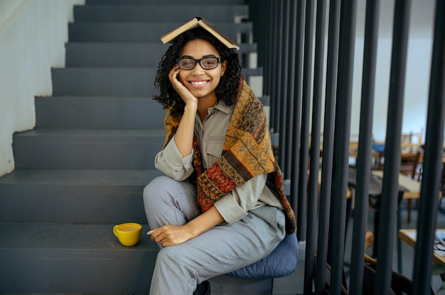 Studentessa graziosa con libro seduto sui gradini nella caffetteria della biblioteca. donna che impara una materia, un'istruzione e una conoscenza. ragazza che studia nel campus