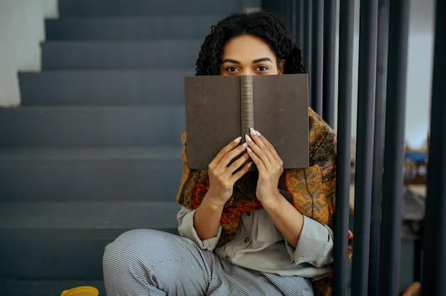 Studentessa graziosa con il libro che si siede sui gradini nella caffetteria della biblioteca