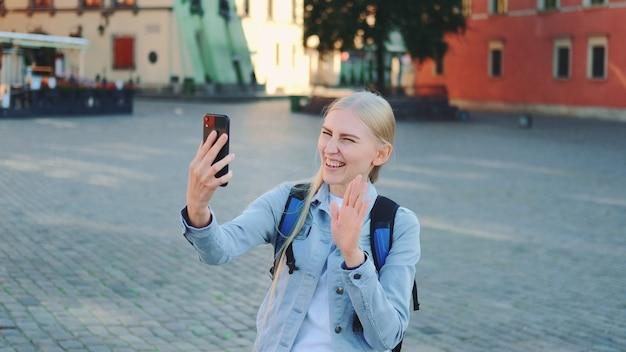 Turista femminile grazioso che effettua videochiamata sullo smartphone dal luogo della sua visita