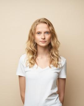 Bella femmina con capelli ricci in maglietta bianca verticale vicino al muro beige