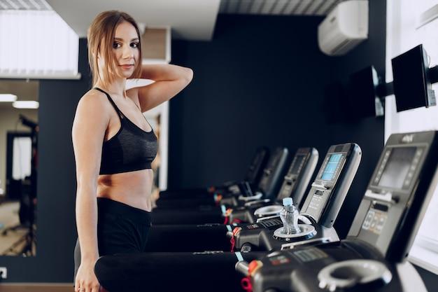Donna abbastanza adatta in allenamento sportrswear nero su un tapis roulant