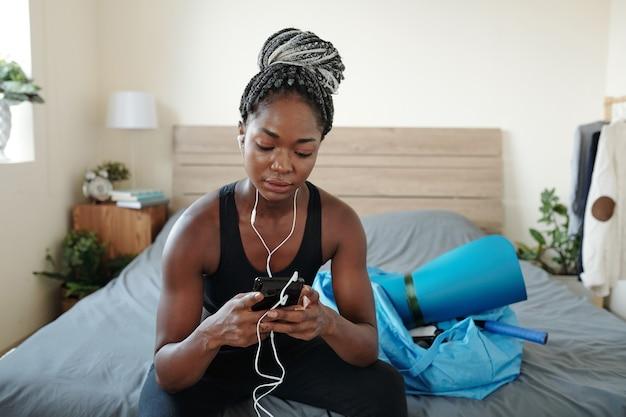 Giovane donna di colore abbastanza in forma seduta sul letto e che sceglie musica per allenarsi nel suo smartphone