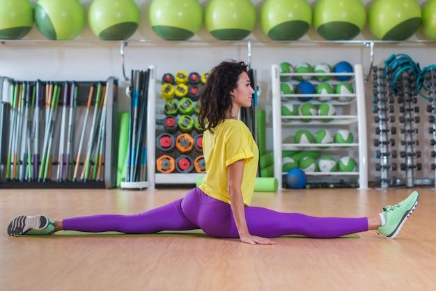 Modello di fitness piuttosto in abiti sportivi facendo spaccatura frontale in palestra, allungando le gambe