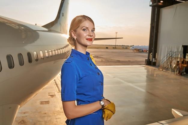 Bella assistente di volo in piedi in uniforme blu e guanti gialli accanto all'aereo in un hangar