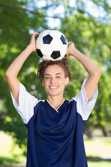 Giocatore di calcio grazioso che sorride alla macchina fotografica