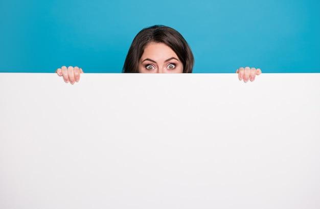 Una signora pazza piuttosto divertente si tiene per mano banner pubblicitario vuoto che sbircia gli occhi