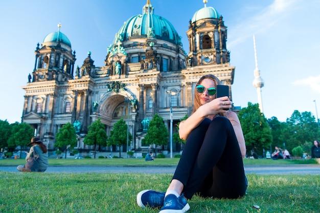 Bella ragazza seduta davanti alla cattedrale di berlino al bellissimo tramonto e facendo selfie