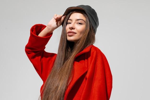 Bella ragazza con cappello nero e cappotto rosso ha alzato le mani e tiene il berretto in studio sul muro bianco
