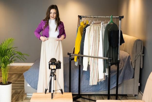 Pretty girl blogger influencer sta mostrando vestiti ai follower per venderli nel negozio online al coperto