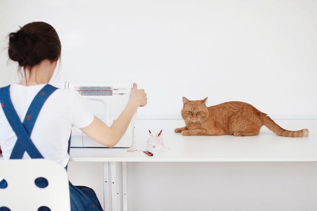 Bella ragazza in un vestito blu cuce su una macchina da cucire, un gatto rosso si siede accanto a lei e guarda