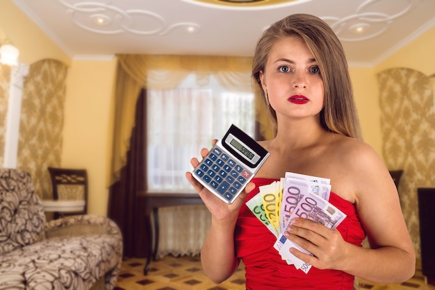 Ragazza graziosa che calcola il pagamento dell'affitto con la fattura dell'euro