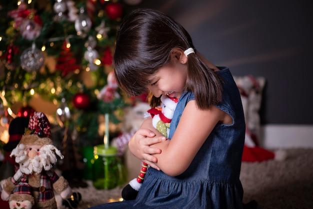 Bella ragazza nella decorazione di natale che abbraccia un pupazzo di neve