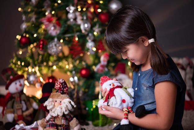 Bella ragazza nella decorazione di natale che gioca con il pupazzo di neve