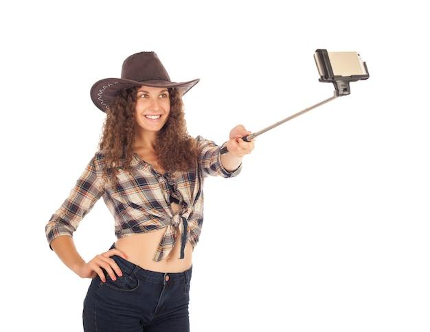 Bella ragazza in stile cowboy che fa selfie sul suo smartphone.