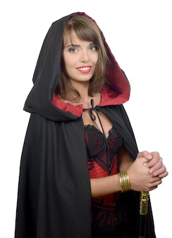 La ragazza graziosa si è vestita in un mantello nero per halloween