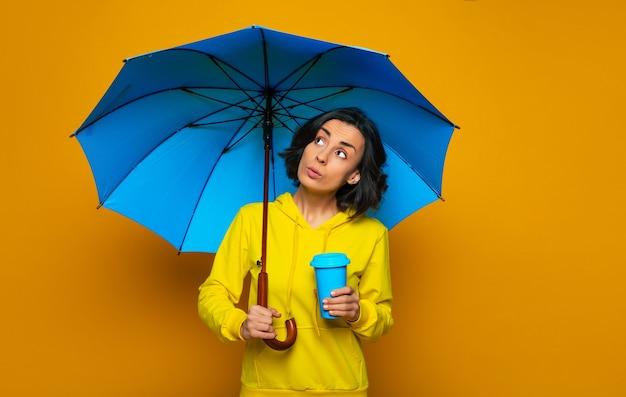 Bella ragazza vestita con una felpa gialla sotto un ombrello, con la tazza termica blu nella mano sinistra, preoccupata per il peggioramento del tempo.