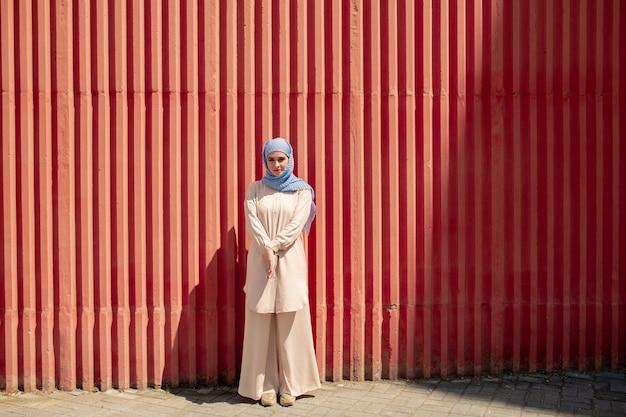 Bella ragazza in hijab e abbigliamento casual in piedi dal muro rosso in ambiente urbano in giornata di sole