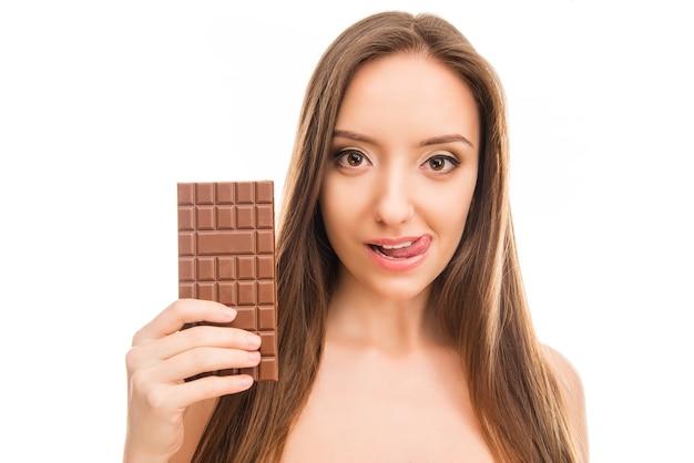 Bella ragazza che tiene la barra di cioccolato e leccandosi le labbra
