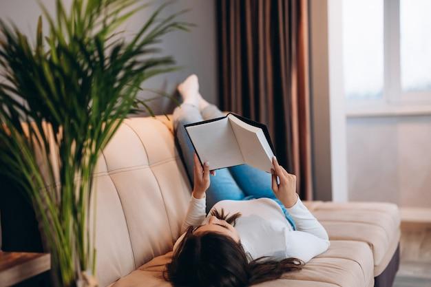 Bella ragazza sta leggendo il libro a casa