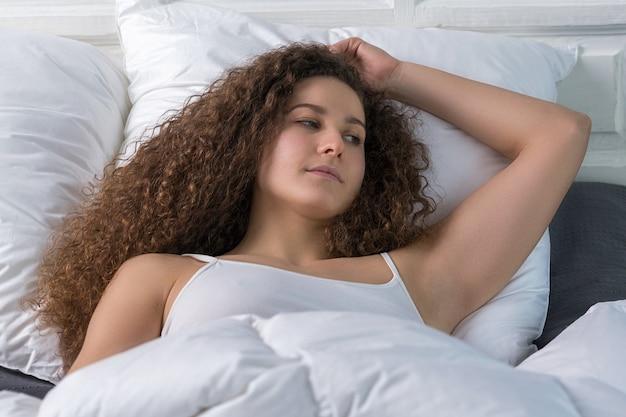 Bella ragazza giace a letto da sola. ha uno sguardo triste.