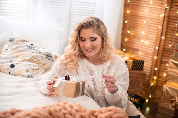 Una bella ragazza in un leggero trucco da sera, seduta sul pavimento vicino al letto, sorridendo apre una scatola con un regalo. regalo di natale, momento felice, felicità delle donne