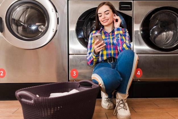 La ragazza graziosa ascolta la musica che si appoggia su una lavatrice nella lavanderia pubblica