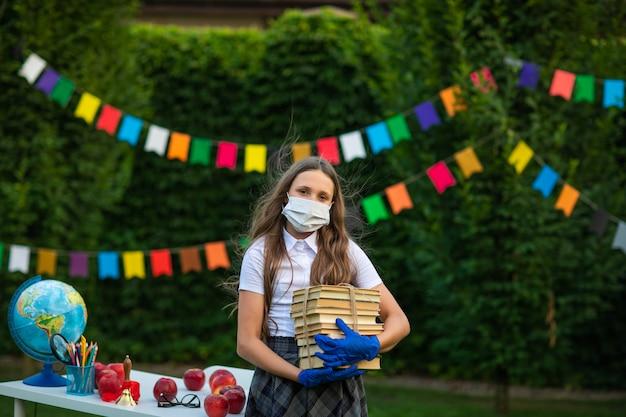 Ragazza graziosa alla maschera medica e guanti che tengono mucchio dei libri contro il fondo delle bandiere