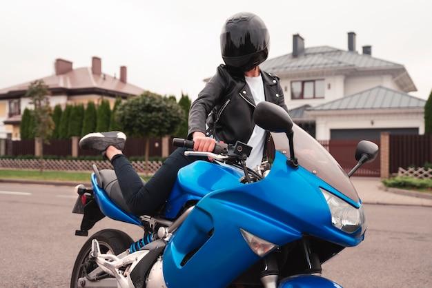 Bella ragazza su una moto con il casco