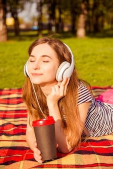 Bella ragazza sul picnic ascoltando musica in cuffia e tenendo la tazza di caffè