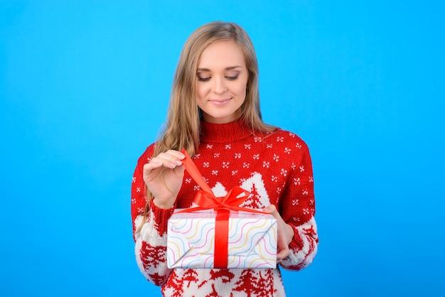 Bella ragazza in pullover scatola di disimballaggio